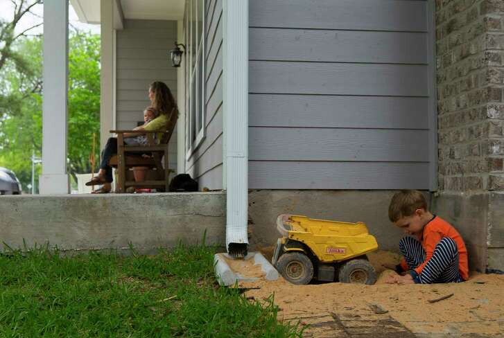 Four year-old Harley Miertschin plays in the sand in the shadow of his family's elevated home along Windswept Lane in the Galleria area, while his mother, Stephanie Miertschin holds her 21-month-old daughter, Elsie, on the family's front porch, Wednesday, March 28, 2018, in Houston. The Miertschin family decided to raise their home after flooding during both the Memorial Day and Tax Day floods. Water did not enter their home during Harvey, but almost all of the other homes in the neighborhood did flood. The street is not in a designated flood plain, and many neighbors blame most of the flooding on downstream drainage problems as the area has become more developed.