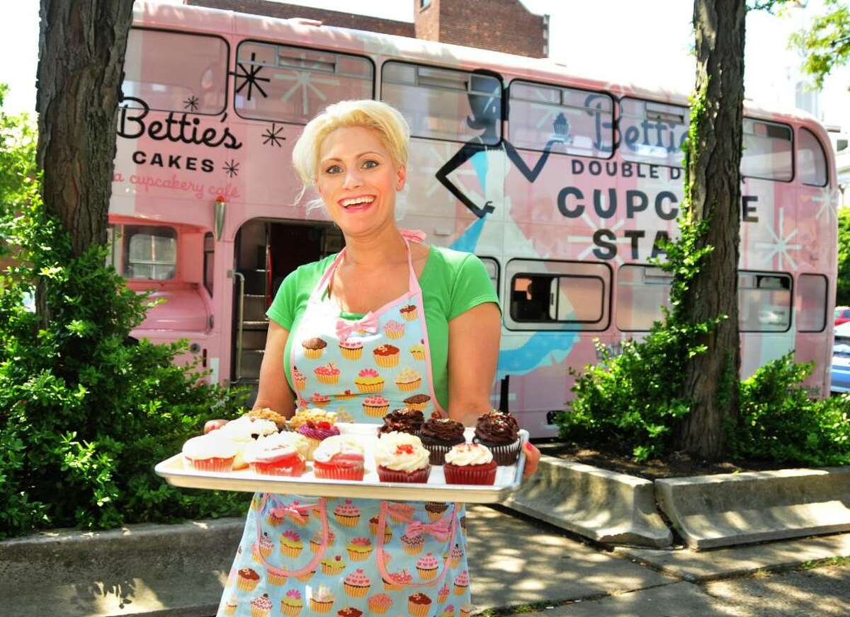 Lorraine Murphy of Bettie's Cakes outside her mobile cafe, a converted English double decker bus parked outside the Schenectady Public Library Tuesday afternoon May 25, 2010. (John Carl D'Annibale / Times Union)