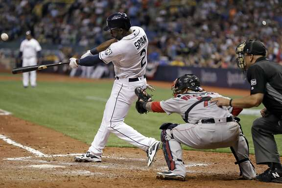 Tampa Bay Rays' Denard Span (2) connects for a three-run triple off Boston Red Sox relief pitcher Carson Smith during the eighth inning of a baseball game Thursday, March 29, 2018, in St. Petersburg, Fla. Red Sox catcher Christian Vazquez, second from right, looks on. (AP Photo/Chris O'Meara)