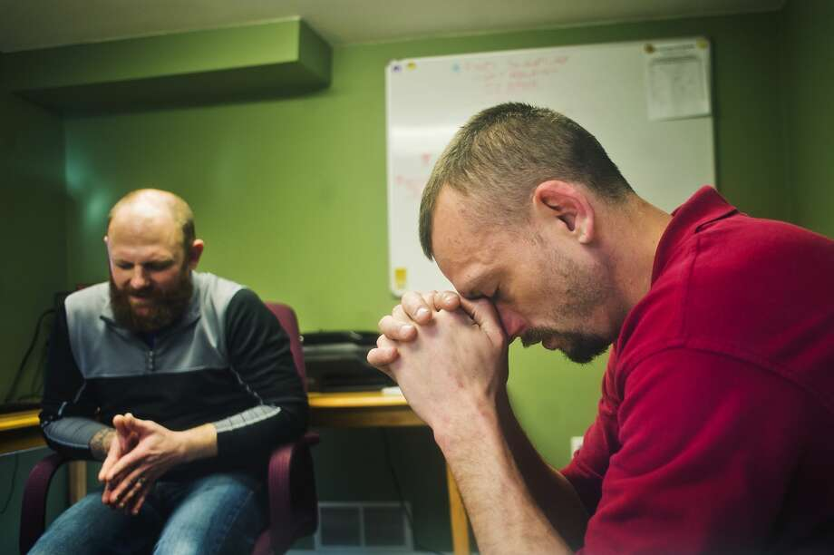 Jeremy Kopke, right, prays with John Phillips, a staff member at Midland's Open Door, during their weekly meeting to monitor Kopke's progress on Monday, March 19, 2018. (Katy Kildee/kkildee@mdn.net) Photo: (Katy Kildee/kkildee@mdn.net)