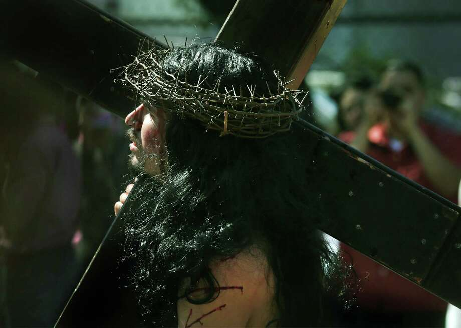 Jesus, portrayed by Andres Mandujano, carries his cross during Good Friday's Passion Play, put on by San Fernando Cathedral which started at Milam Park and ended at Main Plaza in front of San Fernando Cathedral with the crucifixion of Jesus, on Friday, March 30, 2018. Photo: Bob Owen, Staff / San Antonio Express-News / ©2018 San Antonio Express-News