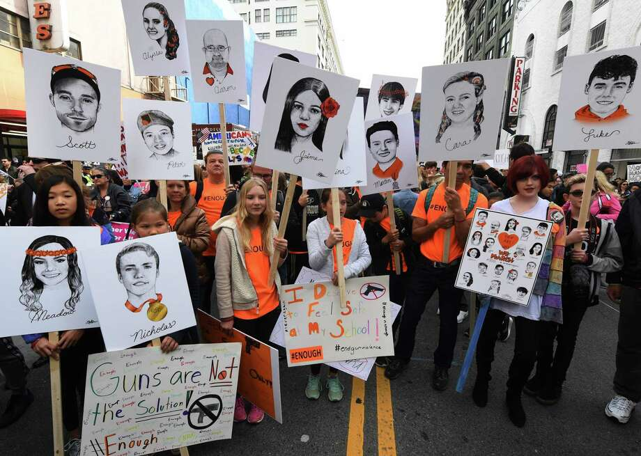 Students hold portraits of victims of Florida's Marjory Stoneman Douglas High School shootings as people protest for tighter gun laws during the student organized 'March For Our Lives' rally in Los Angeles on March 24. Critics say the marchers cast spurious charges against those legitimately supporting gun rights. Photo: MARK RALSTON /AFP /Getty Images / AFP or licensors