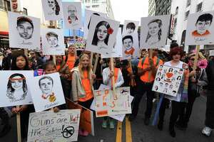 Students hold portraits of victims of Florida's Marjory Stoneman Douglas High School shootings as people protest for tighter gun laws during the student organized 'March For Our Lives' rally in Los Angeles on March 24. Critics say the marchers cast spurious charges against those legitimately supporting gun rights.