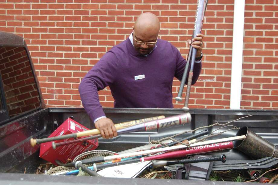 Boys and Girls Club of Greenwich CEO Bobby Walker Jr. removes some baseball bats from the truck of State Rep. Fred Camillo. Camillo led a drive for new and used sports equipment in town for the third year, donating the equipment to the club for use by its members Photo: Ken Borsuk