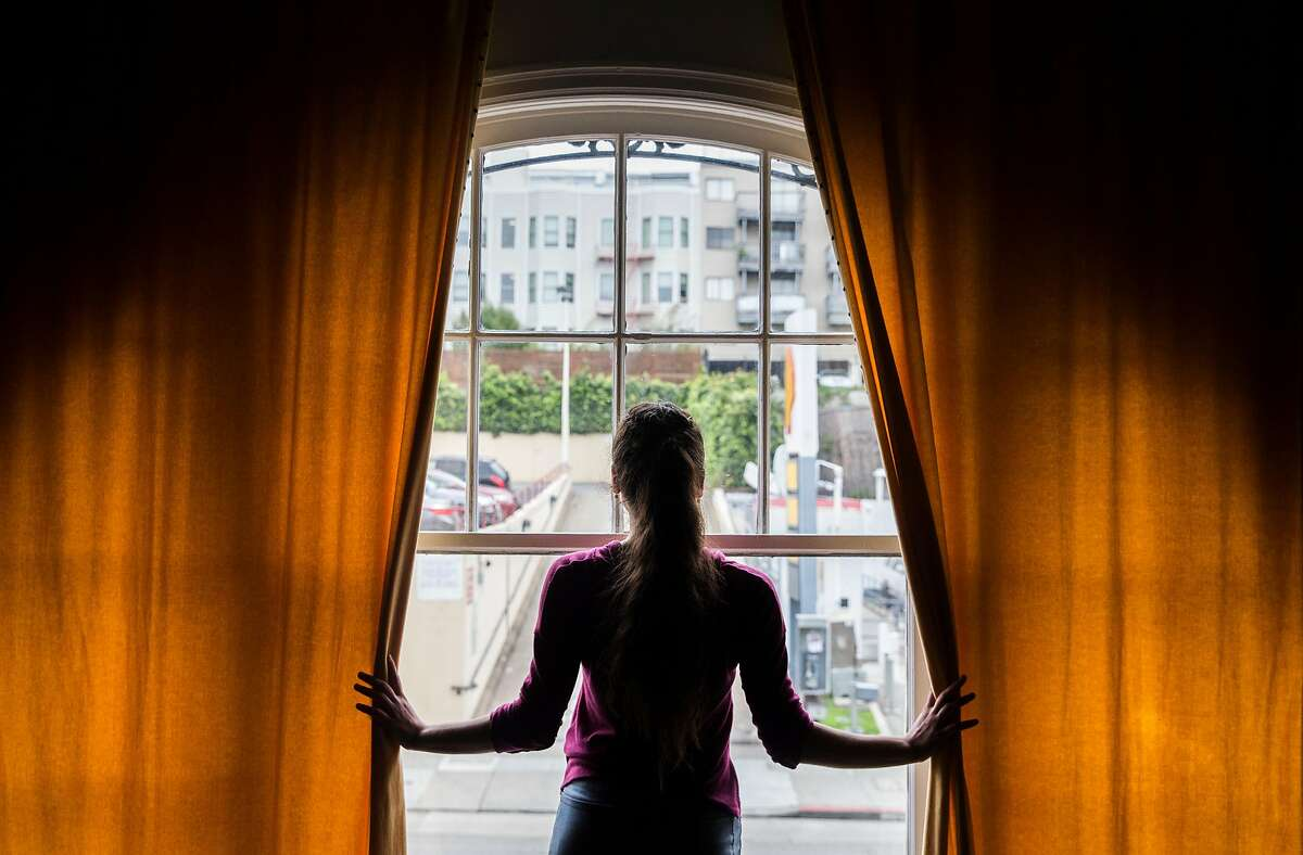 Iris Rocio Davila, 16, of Puerto Rico looks out the window of the communal kitchen inside her apartment building near Franklin Street Wednesday, March 21, 2018 in San Francisco, Calif.