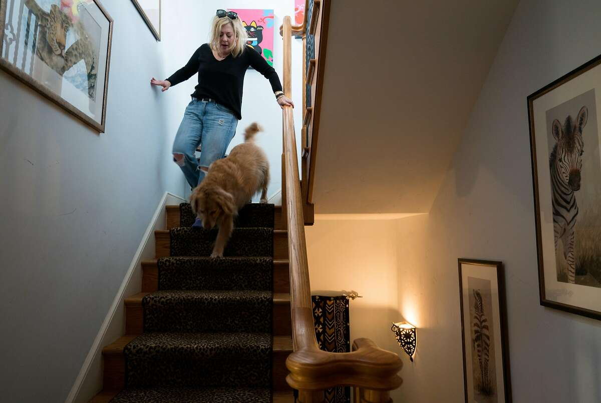 Leigh Anne Varney walks down the stairs with her dog, Callie, inside of her Outer Richmond home in San Francisco, Calif. on Friday, March 30, 2018.
