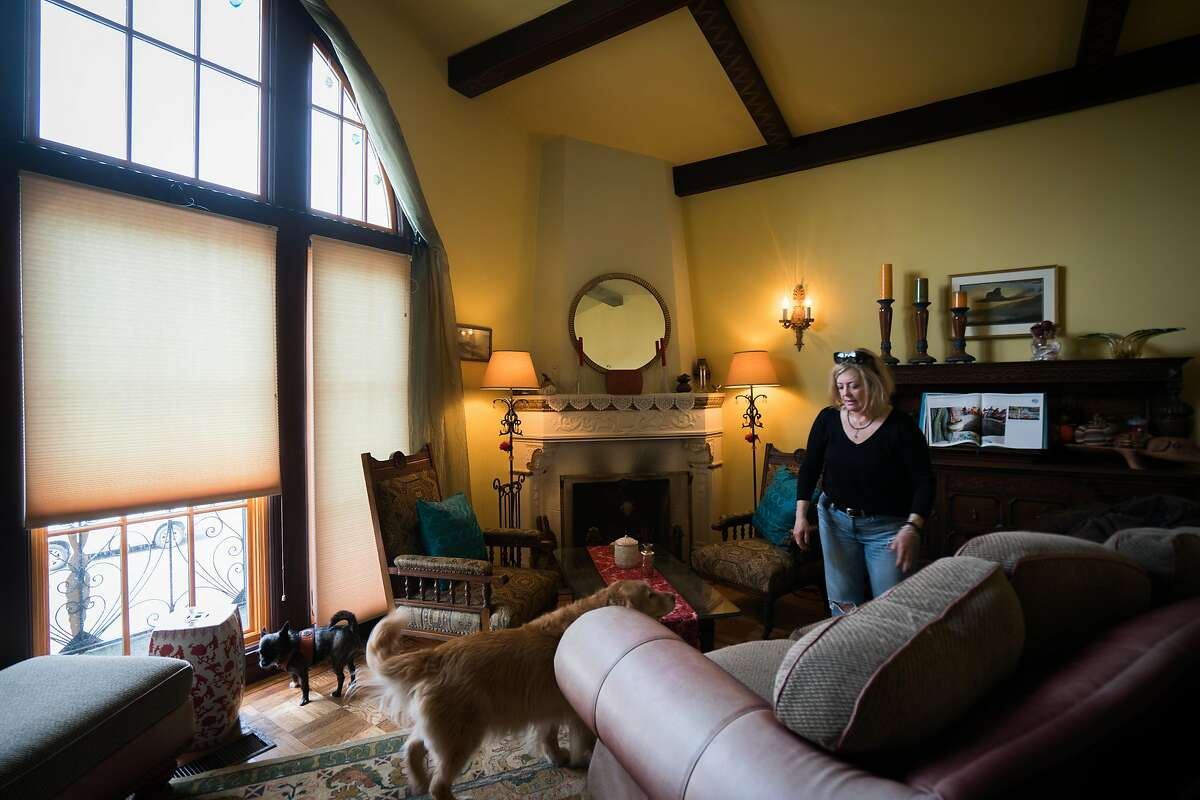 Leigh Anne Varney stands in her living room with her two dogs, Callie and Olive in the Outer Richmond district in San Francisco, Calif. on Friday, March 30, 2018.