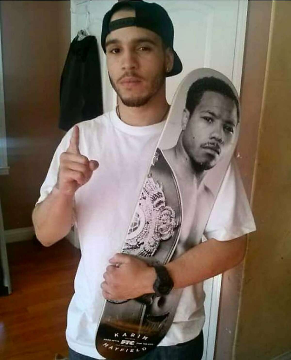 Sahleem Tindle, brother of boxer Karim Mayfield, holds a skateboard with his brother's likeness. Sahleem Tindle was shot and killed by a BART police officer in Oakland back on Jan. 3, 2018. Courtesy Karim Mayfield
