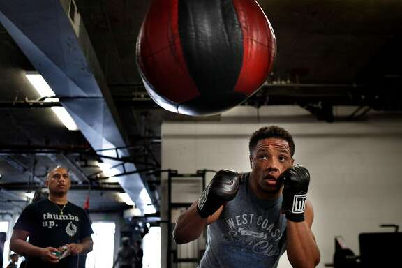 Karim Mayfield works out at the 3rd Street Boxing Gym as his trainer Ben Bautista watches in San Francisco, Calif., on Wednesday, March 28, 2018.  Mayfield is the formerly ranked #3 welterweight boxer in the world, and has started a boxing promotion company and is training for his next fight in April. Karim is coming off of a win last October at the historic San Francisco Armory and since that fight, Karim has been heavily involved in the social/political movements that are protesting the death of his brother, who was recently shot by a Bart police officer.