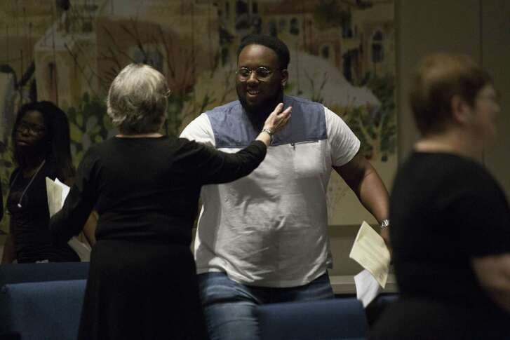 Two Emmanuel Episcopal Church members embrace after the Maundy Thursday service at the Temple Sinai.