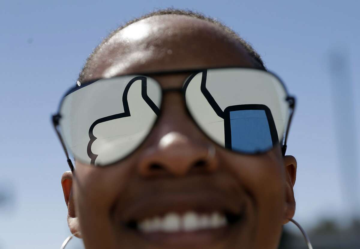 A visitor poses for a photo with the Facebook logo reflected on her sunglasses at the company's headquarters Wednesday, March 28, 2018, in Menlo Park , Calif. (AP Photo/Marcio Jose Sanchez)