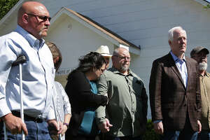 Kathleen Curnow, center, leans into her husband, Fred Curnow, next to pastor Frank Pomeroy, far left, as Senator John Cornyn, far right, stands with church members and survivors during a press conference at First Baptist Church of Sutherland Springs on Friday, March 30, 2018. Cornyn presented survivors with a flag that was flown over the U.S. Capitol on March 23rd, 2018, the day Senator CornynÕs Fix NICS Act was signed into law by President Trump. The Curnows live across from the street.