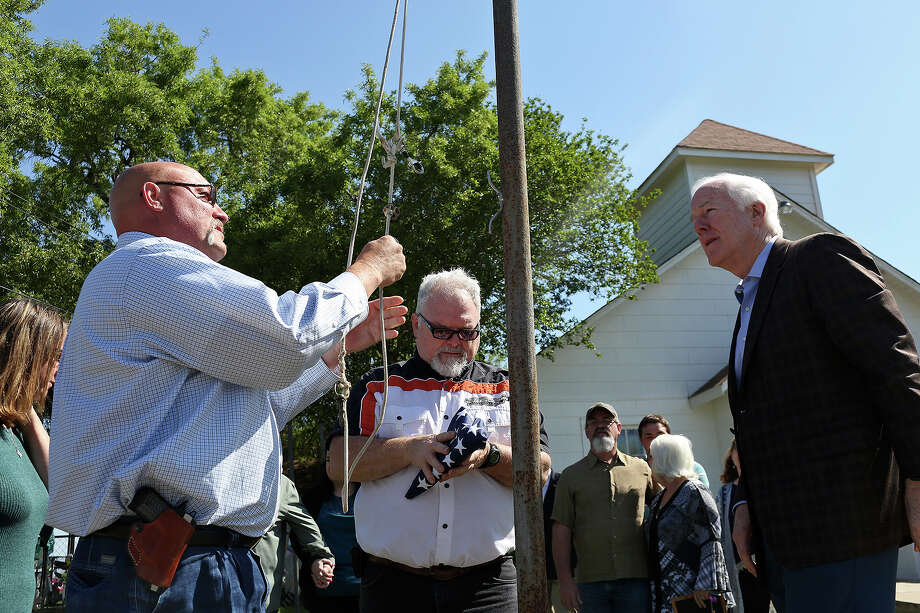 Stephen Willeford, center, opens a flag to be raised by pastor Frank Pomeroy, left, while U.S. Senator John Cornyn, right, watches at First Baptist Church of Sutherland Springs on Friday, March 30, 2018. The flag was flown over the U.S. Capitol on March 23rd, 2018, the day Senator CornynÕs Fix NICS Act was signed into law by President Trump. Photo: SAN ANTONIO EXPRESS-NEWS / SAN ANTONIO EXPRESS-NEWS