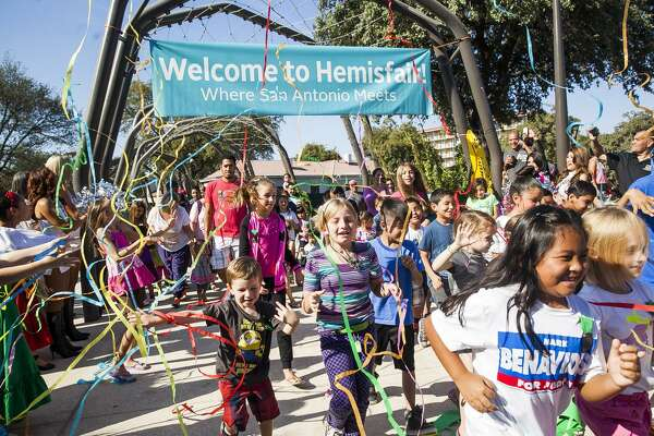 Children run through a banner kicking off the ribbon cutting ceremony at Yanaguana Garden Oct. 3, 2015, at Hemisfair Park.