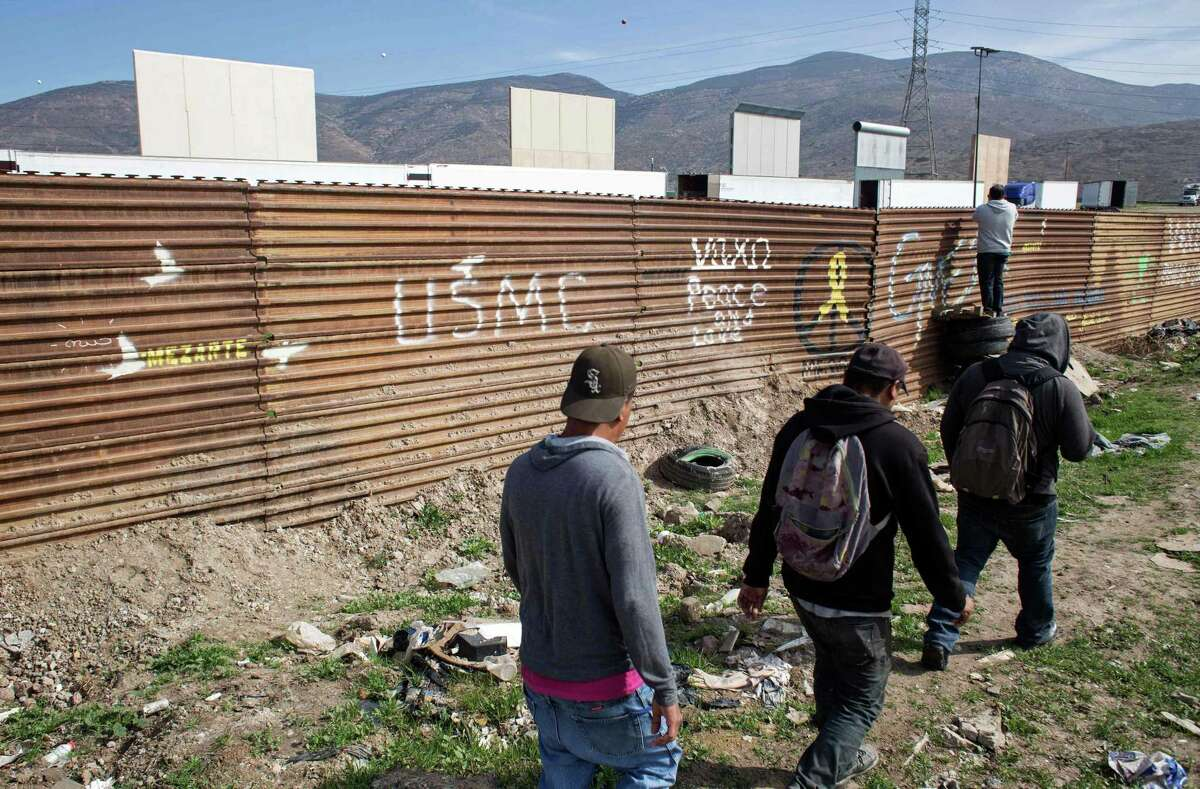 People walk on the Mexican side of the Mexico-U.S. border in Tijuana, from where prototypes of the wall President Donald Trump wants to build on the border with Mexico are visible on the outskirts of San Diego.