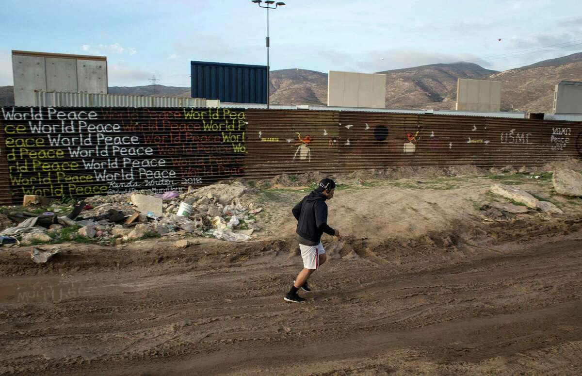 A man jogs on the Mexican side of the Mexico-U.S. border in Tijuana, from where prototypes of the wall President Donald Trump wants to build on the border with Mexico are visible on the outskirts of San Diego.