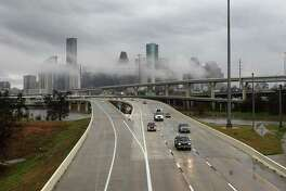 The downtown skyline shrouded in mist after overnight storms dumped several inches of rain as motorists head north on Interstate 45 near Quitman on Feb. 10, 2018, in Houston.