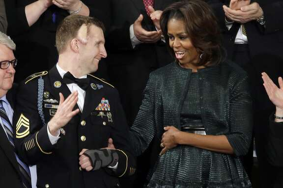 First lady Michelle Obama talks with Army Ranger Sgt. 1st Class Cory Remsburg during President Barack Obama's State of the Union address on Capitol Hill in Washington, Tuesday Jan. 28, 2014. (AP Photo/J. Scott Applewhite)