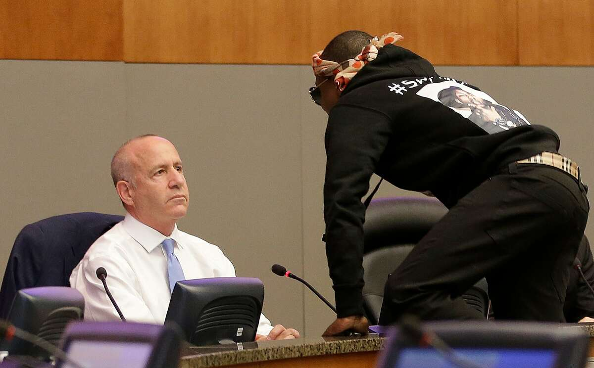Stevante Clark jumps on the dais and shouts at Sacramento Mayor Darrell Steinberg, left, during a city council meeting in Sacramento, Calif., on Tuesday, March 27, 2018. Stevante, the brother of Stephon Clark who was shot and killed by Sacramento Police officers a week earlier, disrupted the meeting and demanded to speak. The city council adjourned for a roughly 15-minute recess as a result of the disruption. (AP Photo/Rich Pedroncelli)
