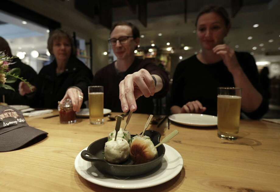 In this Friday, March 9, 2018 photo, Mike Hardin, center, reaches for a dumpling while dining with other taking a tour with Avital Food Tours at China Live in San Francisco. Avital Tours runs excursions in San Francisco and Los Angeles that take diners to restaurants for progressive dinners, each course is served at a different restaurant. While inflation overall has been tame the past few years, many small businesses nonetheless have seen their costs rise, especially for labor and energy. (AP Photo/Jeff Chiu) Photo: Jeff Chiu, STF / Associated Press / Copyright 2018 The Associated Press. All rights reserved.