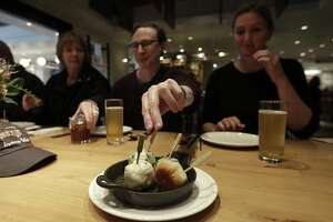In this Friday, March 9, 2018 photo, Mike Hardin, center, reaches for a dumpling while dining with other taking a tour with Avital Food Tours at China Live in San Francisco. Avital Tours runs excursions in San Francisco and Los Angeles that take diners to restaurants for progressive dinners, each course is served at a different restaurant. While inflation overall has been tame the past few years, many small businesses nonetheless have seen their costs rise, especially for labor and energy. (AP Photo/Jeff Chiu)