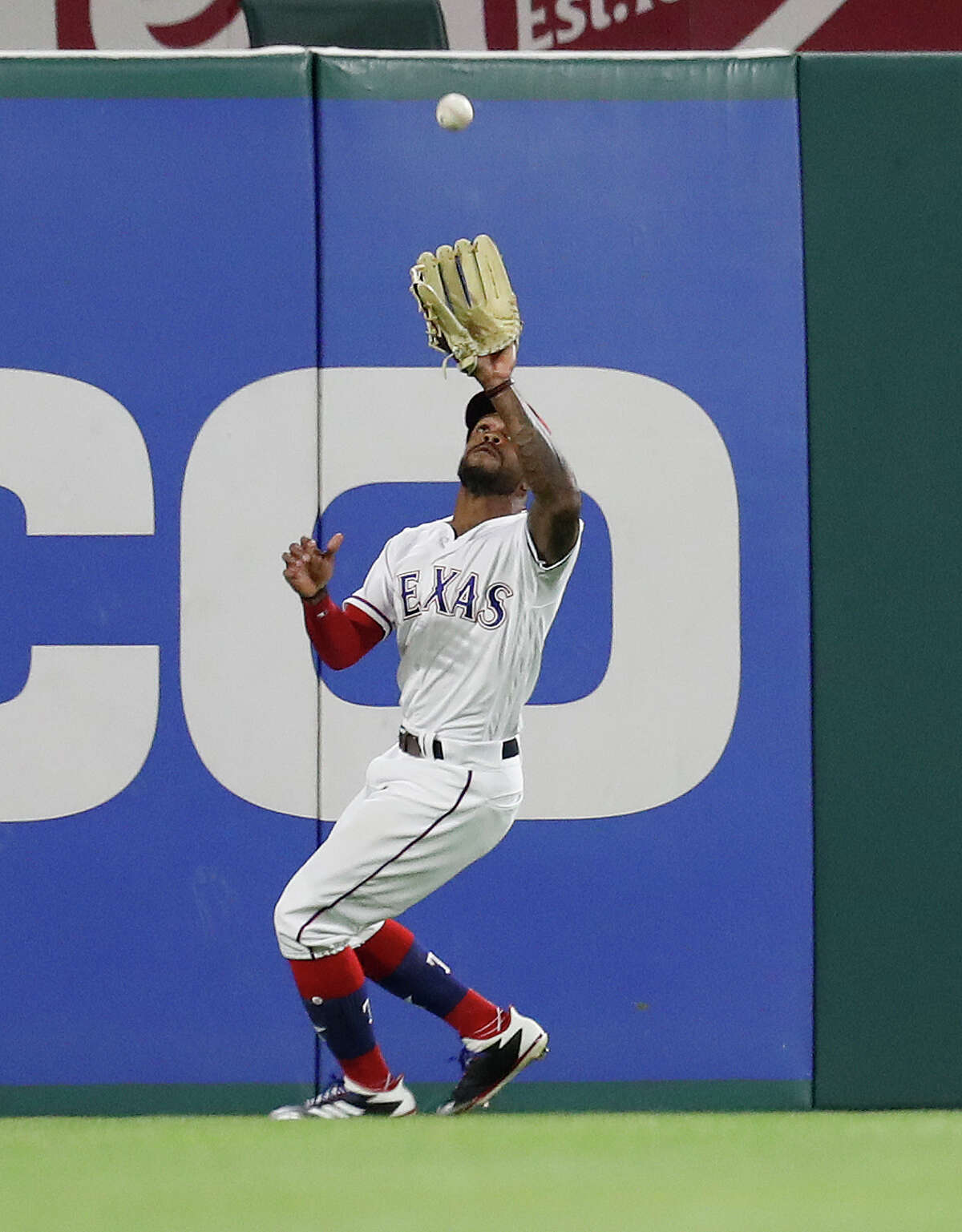 Texas Rangers left fielder Delino DeShields (3) catches Houston Astros center fielder George Springer's ball on the warning track in the fifth inning of an MLB baseball game Globe Life Park, Friday, March 30, 2018, in Arlington.