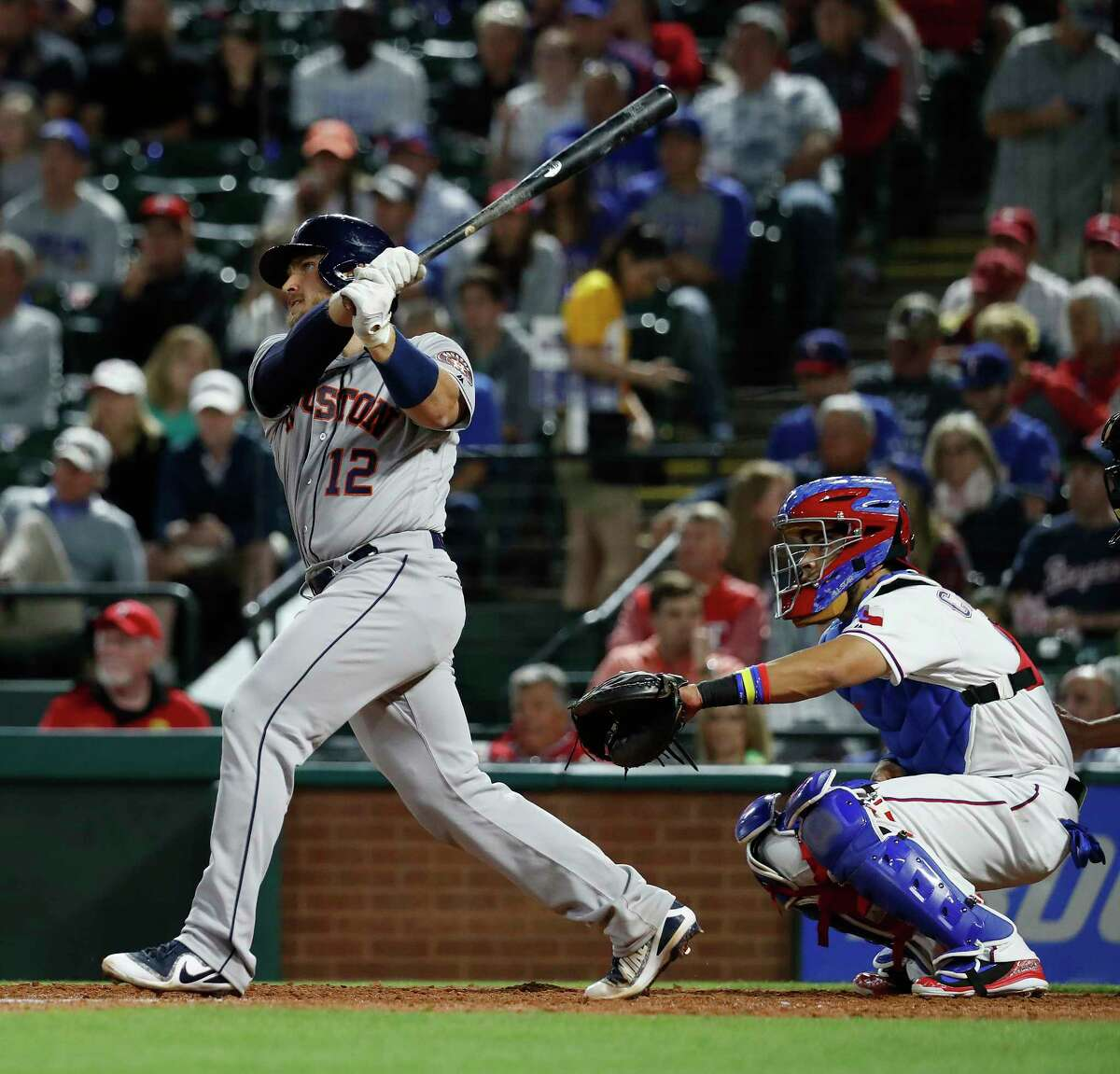 Houston Astros catcher Max Stassi (12) hits an RBI double in the fifth inning of an MLB baseball game Globe Life Park, Friday, March 30, 2018, in Arlington.