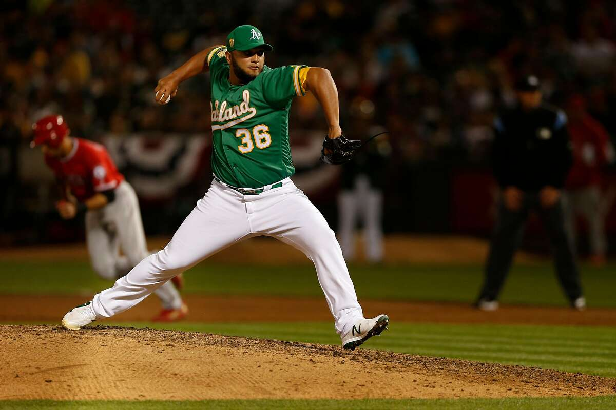 Oakland Athletics relief pitcher Yusmeiro Petit (36) throws for a ground out to end the inning as Los Angeles Angels shortstop Andrelton Simmons (2) tries to steal during an MLB game between the Oakland Athletics and Los Angeles Angels at the Oakland Coliseum, Friday, March 30, 2018, in Oakland, Calif.