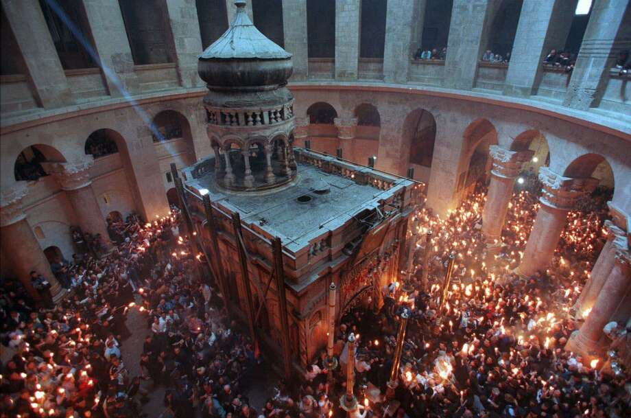 Thousands of pilgrims hold candles as they surround the empty tomb where it is believed Jesus was buried, inside the Church of the Holy Sepulchre in Jerusalem during the Christian Orthodox ceremony of the Holy Fire, which celebrates Christ's resurrection. (AP Photo/Ruth Fremson) Photo: RUTH FREMSON, STF / AP / AP