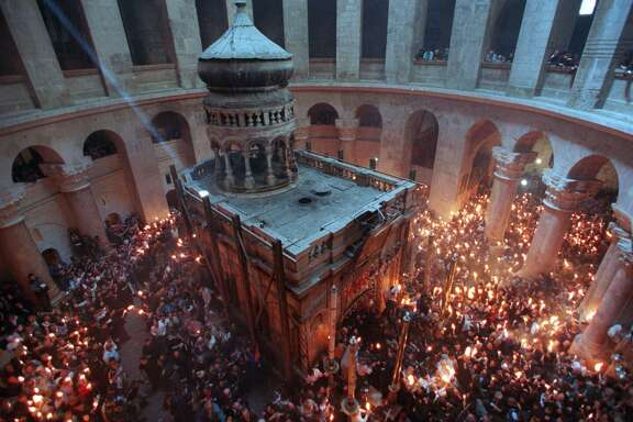Thousands of pilgrims hold candles as they surround the empty tomb where it is believed Jesus was buried, inside the Church of the Holy Sepulchre in Jerusalem during the Christian Orthodox ceremony of the Holy Fire, which celebrates Christ's resurrection. (AP Photo/Ruth Fremson)