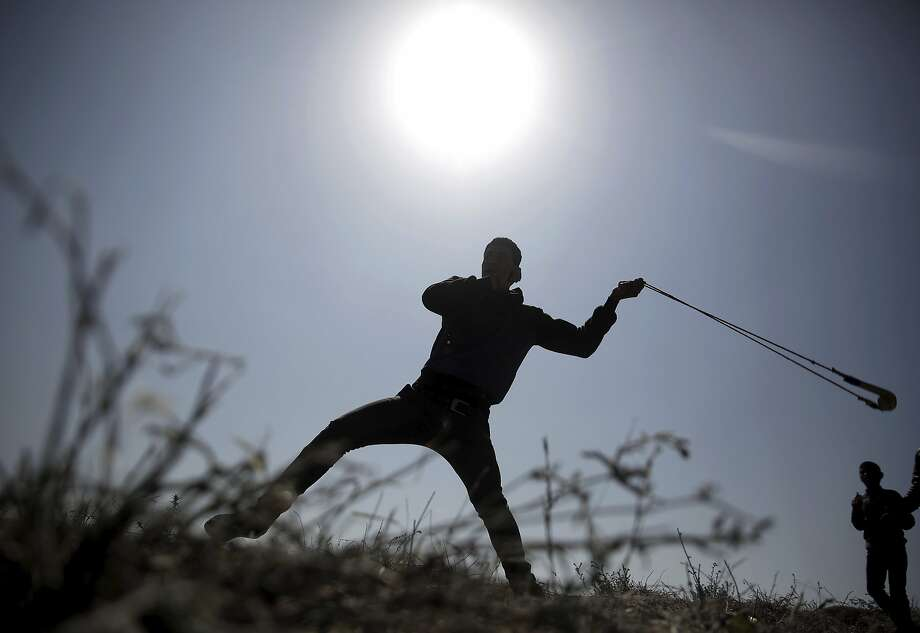 A Palestinian protester hurls stones toward Israeli soldiers during a protest near the Gaza Strip border with Israel, in eastern Gaza City, Saturday, March 31, 2018. (AP Photo/ Khalil Hamra) Photo: Khalil Hamra / Associated Press