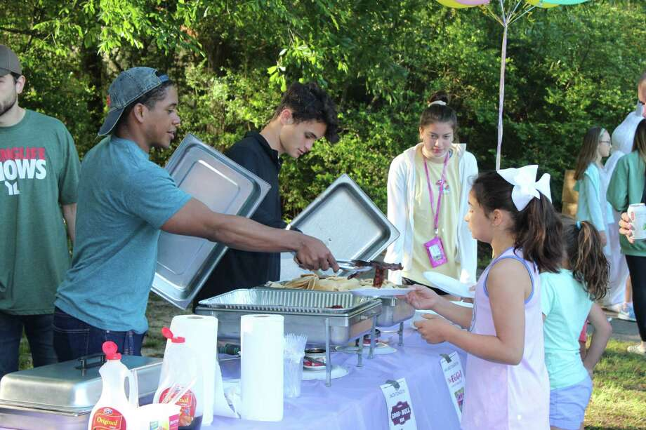 Montgomery County Young Life volunteers pass out free pancakes and bacon during the annual Pancake Party at Meadowlake Park on Saturday, March 31. Photo: Staff Photo By Patricia Dillon