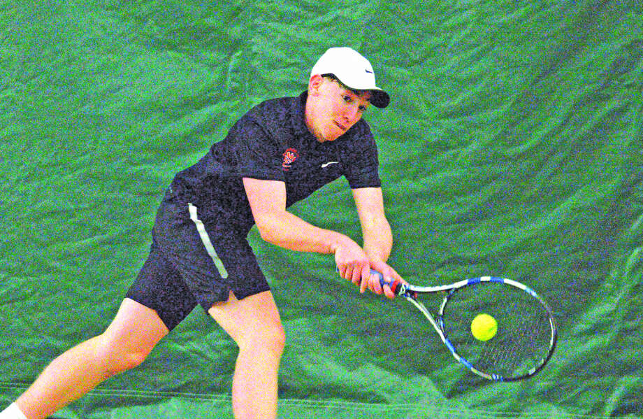 Edwardsville senior Logan Pursell hits a two-handed backhand during his No. 4 singles match against John Burroughs on Saturday at the Edwardsville Meyer Center YMCA.
