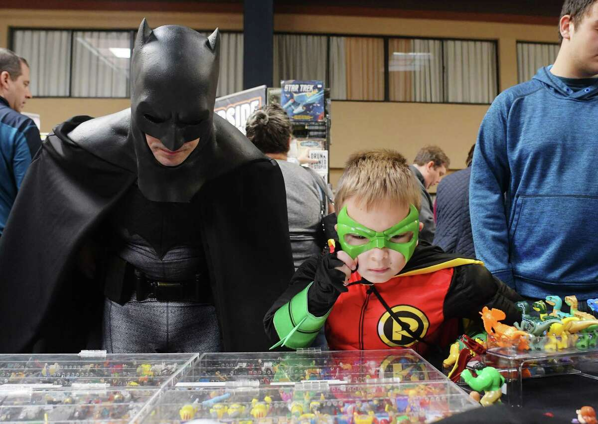 Erik Nussbaum, left, from Queensbury, dressed as Batman, and his son Connor, 8, dressed as Robin, look over some of the items for sale at the Toying Around booth at the 7th annual Albany Comic Con at the Radisson Hotel on Sunday, Oct. 30, 2016, in Albany, N.Y. Nussbaum and his son also volunteer for Make A Wish and March of Dimes events, where they come as Batman and Robin. (Paul Buckowski / Times Union)