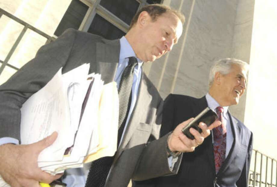 Attorney Abbe D. Lowell, left, checks his phone as former Senate Majority Leader Joseph L. Bruno, right, comments to the press after leaving the Federal Courthouse in Albany on Oct. 26, 2009. (Skip Dickstein/Times Union)