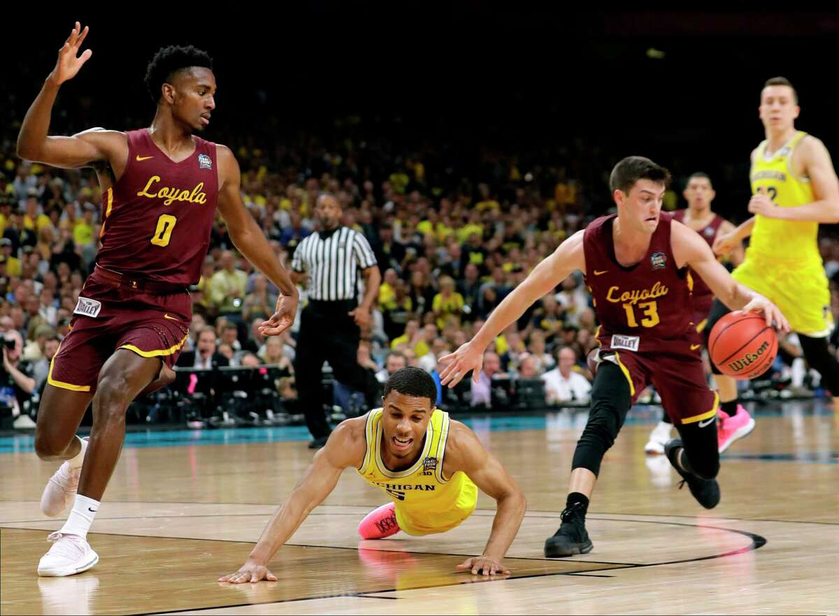 Michigan guard Jaaron Simmons, center, fights for a loose ball with Loyola-Chicago's Donte Ingram, left, and Clayton Custer, right, during the first half in the semifinals of the Final Four NCAA college basketball tournament, Saturday, March 31, 2018, in San Antonio.