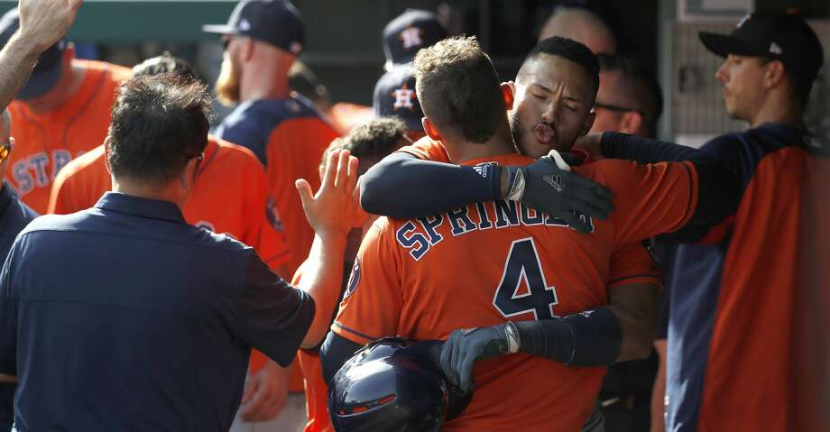 Houston Astros shortstop Carlos Correa (1) hugs Houston Astros center fielder George Springer (4) after hitting a two-run home run in the seventh inning of an MLB baseball game at Globe Life Park, Saturday, March 31, 2018, in Arlington.   ( Karen Warren / Houston Chronicle ) Photo: Karen Warren/Houston Chronicle