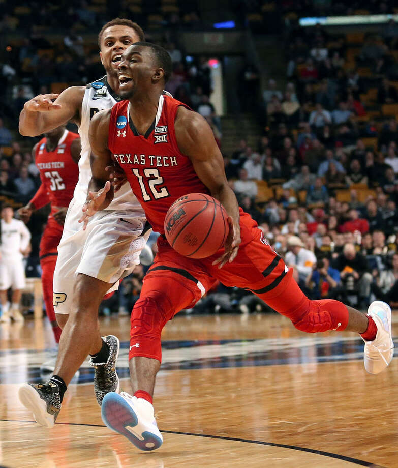 Texas Tech's Keenan Evans dribbles past Purdue's P.J. Thompson, rear, during the second half of an NCAA men's college basketball tournament regional semifinal Friday, March 23, 2018, in Boston. (AP Photo/Mary Schwalm)