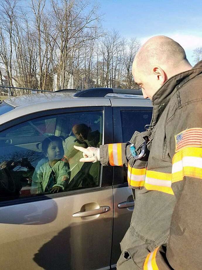 A Danbury, Conn., fire lieutenant distracted a young girl as other fire personnel worked to unlock her mother's minivan door that she was locked inside of on Saturday, March 31, 2018. Photo: Contributed Photo / Danbury Fire Department / Contributed Photo / Connecticut Post Contributed