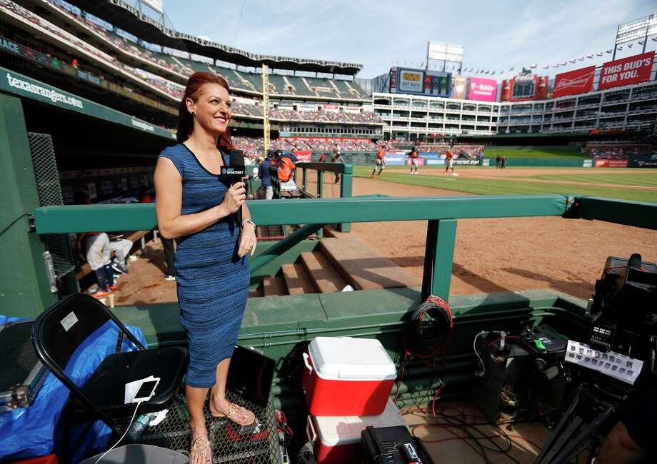 Julia Morales, field reporter and host for AT&T SportsNet reports from inside the third base photo well in the sixth inning of an MLB baseball game at Globe Life Park, Saturday, March 31, 2018, in Arlington. Photo: Karen Warren, Houston Chronicle / © 2018 Houston Chronicle