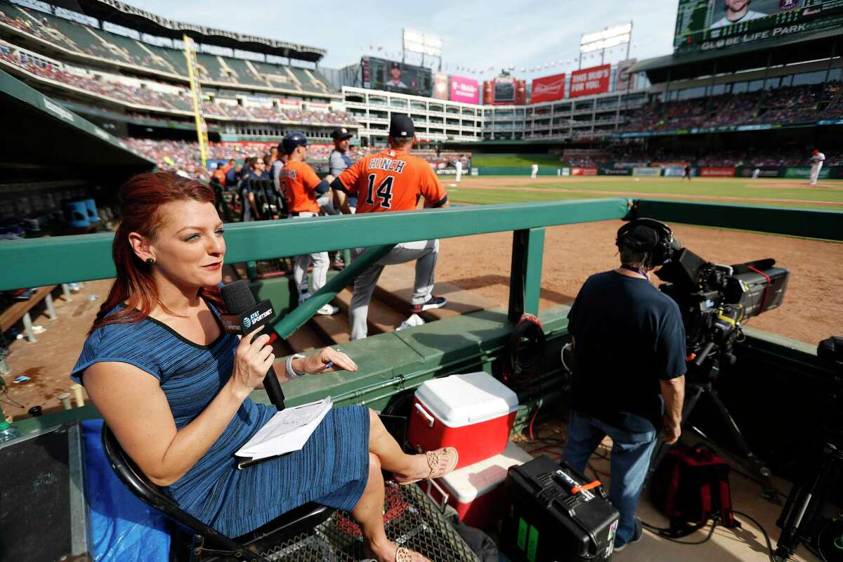 Julia Morales, field reporter and host for AT&T SportsNet reports from inside the third base photo well in the sixth inning of an MLB baseball game at Globe Life Park, Saturday, March 31, 2018, in Arlington.