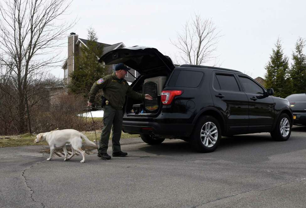 An FBI sniffer dog is brought to the home of NXIVM co-founder Nancy Salzman which was raided by federal agents on Tuesday, March 27, 2018, in Halfmoon, N.Y. Keith Raniere, the co-founder of the NXIVM corporation has been arrested by the FBI based on a federal criminal complaint filed in the Eastern District of New York. (Will Waldron/Times Union)