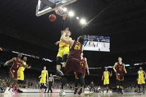 Moritz Wagner jams a shot down for the Wolverines against Cameron Krutwig as Loyola Chicago plays Michigan in the first round of the NCAA National Basketball Championships at the Alamodome on March 31, 2018.