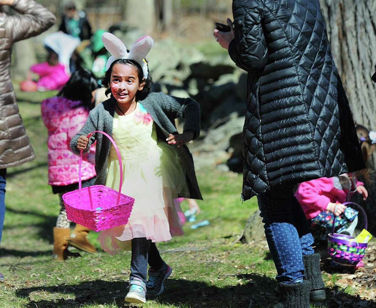"""Anoo Subbu, 6, of Stamford, during the annual Easter Egg Hunt at the St. Francis Episcopal Church in Stamford Saturday morning. Church parishioner Tyler Stevens who was one of the organizers of the event and who wore easter bunny ears to """"get in the spirit of the event,"""" also said that thousnads of eggs with treats were placed around the church for the many kids particiapting. Stevens also said """"We started the egg hunt a little early this year. The kids were doing face painting but were getting ansty for the egg hunt."""" St. Francis Episcopal Church Rev. Mark Lingle said about the annual event, the 10th the church has held, """"Just fantastic. Lots of young kids. It was great, from the arts & crafts and especially the egg hunt. Fantastic."""""""