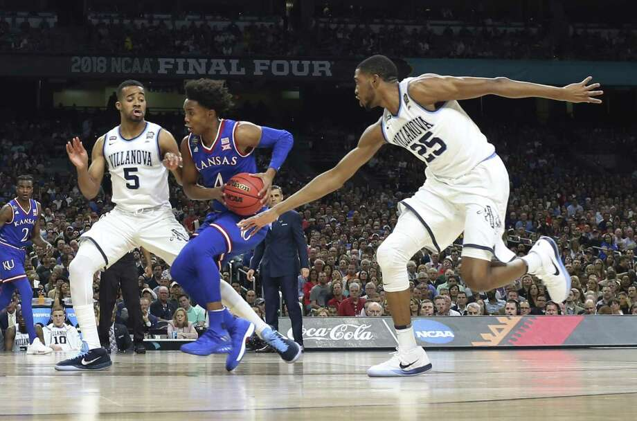 Kansas' Devonte' Graham (4) drives between Villanova's Phil Booth (5) and Mikal Bridges (25) during their National Semifinal game of the NCAA Final Four tournament at the Alamodome on Saturday, Mar. 31, 2018. (Kin Man Hui/San Antonio Express-News) Photo: Kin Man Hui, Staff / San Antonio Express-News / ©2018 San Antonio Express-News