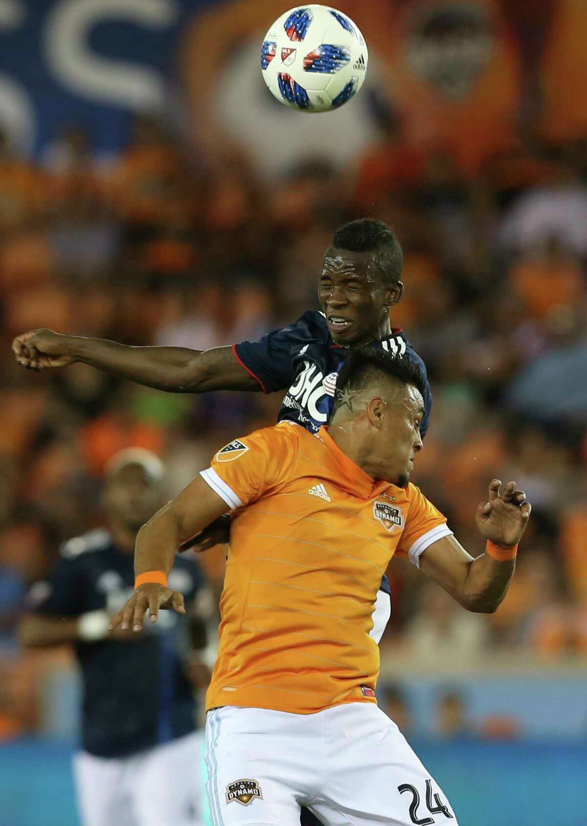 Houston Dynamo midfielder Darwin Ceren (24) and New England Revolution midfielder Luis Caicedo (27) go up for a header during the first half of the MLS game at BBVA Compass Stadium on Saturday, March 31, 2018, in Houston.