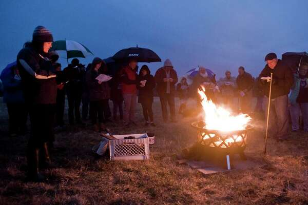 Reverend Jennifer Whipple, of the Congregational Church of Brookfield, leads a hymn during the Easter Sunrise Service at Happy Landings Open Space in Brookfield. Sunday, April 1, 2018