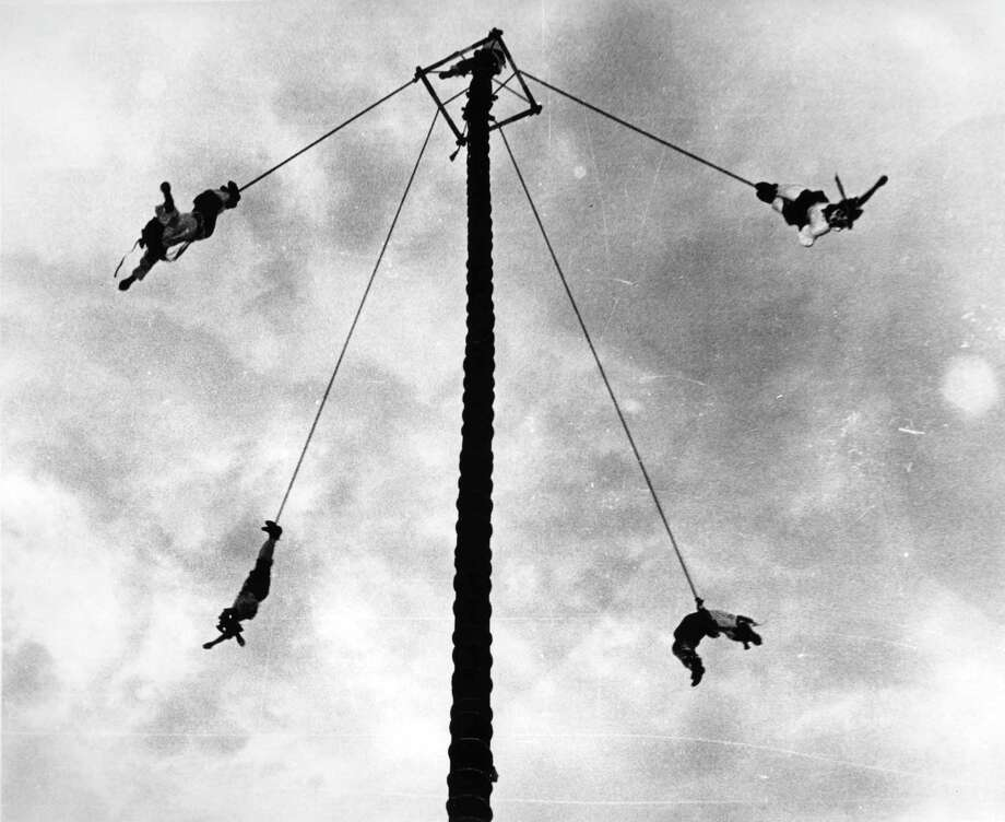 """Los Voladores de Papantla,"" or ""The Flying Indians,"" entertained crowds with an act performed with ropes on a tall pole that swung performers in a radius of 32 feet before they reached the ground. Photo: Courtesy UTSA Special Collections / Institute of Texan Cultures"