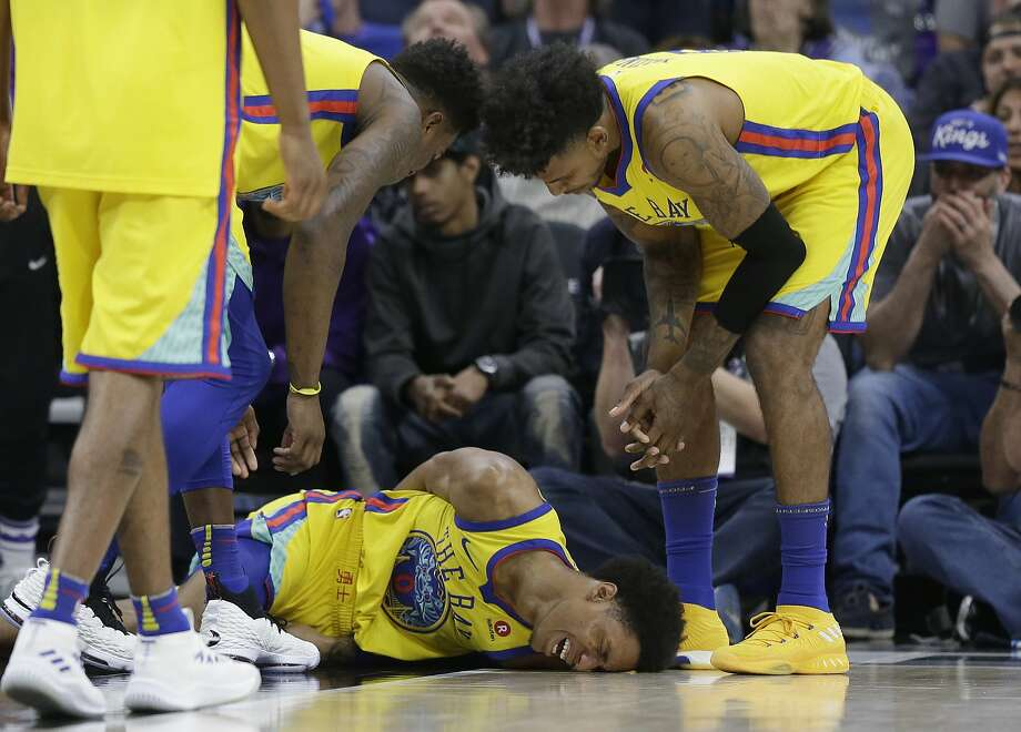 Golden State Warriors guard Patrick McCaw lays on the court in pain as teammates Jordan Bell, left and Nick Young check on his condition after falling hard to the floor late in the third quarter following a Flagrant 1 foul by Sacramento Kings's Vince Carter in an NBA basketball game Saturday, March 31, 2018, in Sacramento, Calif. McCaw was taken off the court on a stretcher. The Warriors won 112-96. (AP Photo/Rich Pedroncelli) Photo: Rich Pedroncelli, Associated Press