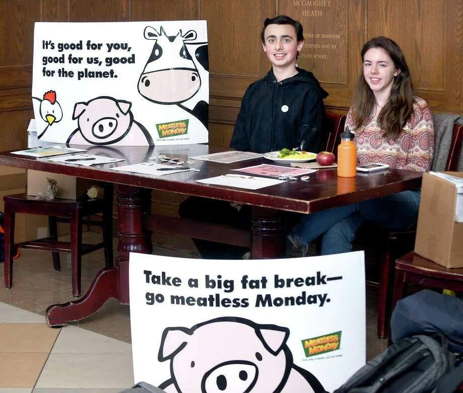 Freshmen Jack Kealey, left, and Sophie Sonnenfeld outside of the Heath Dining Room where they are encouraging classmates to sign a meatless pledge at Hopkins School in New Haven on Monday. Photo: Arnold Gold / Hearst Connecticut Media / New Haven Register